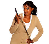 Surprised young woman looking to phone handset — Stock Photo