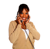 Happy young female smiling and conversing on phone — Stock Photo