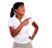 Ethnic young woman pointing and looking right — Stock Photo