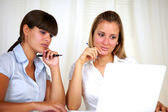 Reflective or pensive young businesswomen reading — Stock Photo