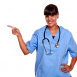 Smiling young nurse looking at you pointing right — Stock Photo #16296989