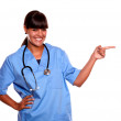 Smiling young nurse looking at you pointing left — Stock Photo #16791489