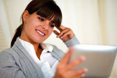 Smiling young female reading on tablet pc screen — Stock Photo
