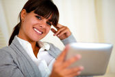 Smiling woman looking at you reading on tablet pc — ストック写真
