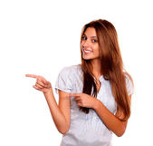 Smiling young woman pointing to her right — Stock Photo