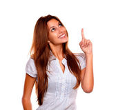 Smiling young woman looking and pointing up — Stock Photo