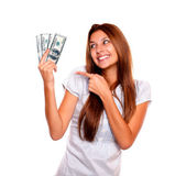Smiling woman looking and pointing cash money — Stock Photo