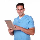 Charming nurse man using his tablet pc — Stock Photo