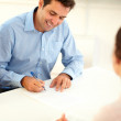 Smiling handsome businessman sign a contract — Stock Photo