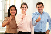 Professional team smiling at you with ok thumb — Stock Photo