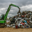 A green hydraulic equipment working in a scrap yard full of different objects — Stok fotoğraf #47920191