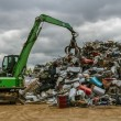 A green hydraulic equipment working in a scrap yard full of different objects — ストック写真 #47920191