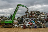 A green hydraulic equipment working in a scrap yard full of different objects — Stock Photo