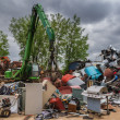 A green hydraulic equipment working in a scrap yard full of different objects — Stok fotoğraf #47980323