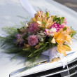 Stock Photo: Wedding bouquet on front hood of car