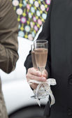 Glass of champagne in a hand of the groom — Stock Photo