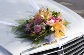 Wedding bouquet on a front hood of a car — Stock Photo