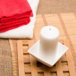 Spa concept with towels and candle — Stock Photo