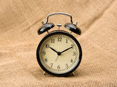 Alarm clock on linen — Stockfoto