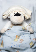 Bear in bed with thermometer — Stock Photo
