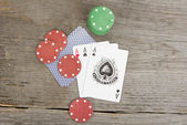 Playing cards and poker chips on wooden background — Stock Photo