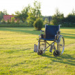 Stock Photo: Empty wheelchair over green grass