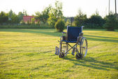 Empty wheelchair over green grass — Stock Photo