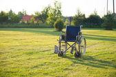 Empty wheelchair over green grass — Stock Photo