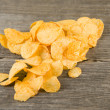 Crunchy potato chips on wooden background — Stock Photo
