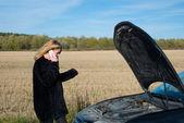 Vacker blond tjej ringer mobiltelefon nära hennes trasiga bil — Stockfoto