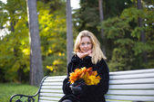 Beautiful girl on bench with leaves — Stock Photo