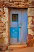 Old textured door in a stone wall — Stock Photo