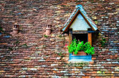 Old orange brick roof with window and flowers — Stock Photo