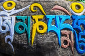 Tibetan buddhist religious symbols on stones — Stock Photo