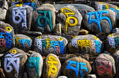 Tibetan religious budhist symbols on stones — Stock Photo