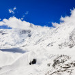 Snow mountain peak with clouds and blue sky — Stock Photo