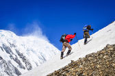 Two mountain trekkers on snow with peaks background — Stock Photo