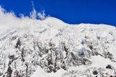 Sneeuw bergtop met gletsjer, wolken en blauwe hemel — Stockfoto