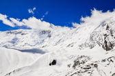 Sneeuw bergtop met wolken en blauwe hemel — Stockfoto
