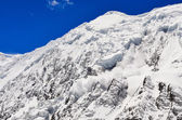 Avalanche falling from snowy frozen mountain peak — Stock Photo