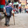 Stock Photo: Poor old man walking with stick in exotic asian street