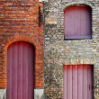Old vintage brick wall with red wooden doors and windows — Stock Photo