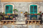 Beautiful vintage balcony with colorful flowers and doors — Stock Photo