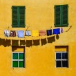 Detail of colorful yellow house walls, windows and clothes — Stock Photo #32713181