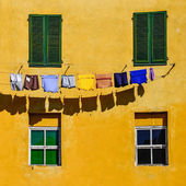 Detail of colorful yellow house walls, windows and clothes — Stock Photo