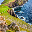 Vertical view of Neist Point lighthouse and rocky ocean coastlin — Stock Photo