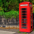Typical red English telephone booth in the park — Stock Photo