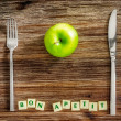 Silverware and apple on wooden table with Bon apetit sign — Stock Photo