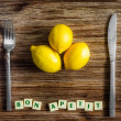 Silverware and lemons on wooden table with Bon apetit sign — Stock Photo