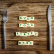 Silverware on table and Good food served here sign — Stock Photo